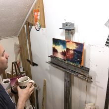 Brad Blackman examining works-in-progress while drinking coffee