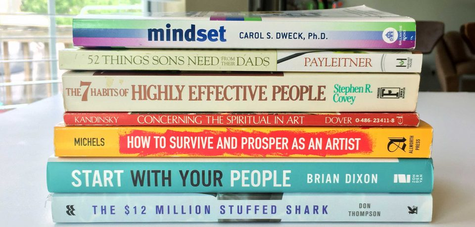 Brad Blackman's Reading Stack for Summer 2020 includes Mindset by Carol S. Dweck, 52 Things Sons Need from their Dads by Jay Payleitner, The 7 habits of Highly Effective People by Stephen R. Covey, Concerning the Spiritual in Art by Wassily Kandinsky, How to Survive and Prosper as an Artist (7th Edition) by Carroll Michels, Start with Your People by Brian Dixon, and The $12 Million Stuffed Shark by Don Thompson.