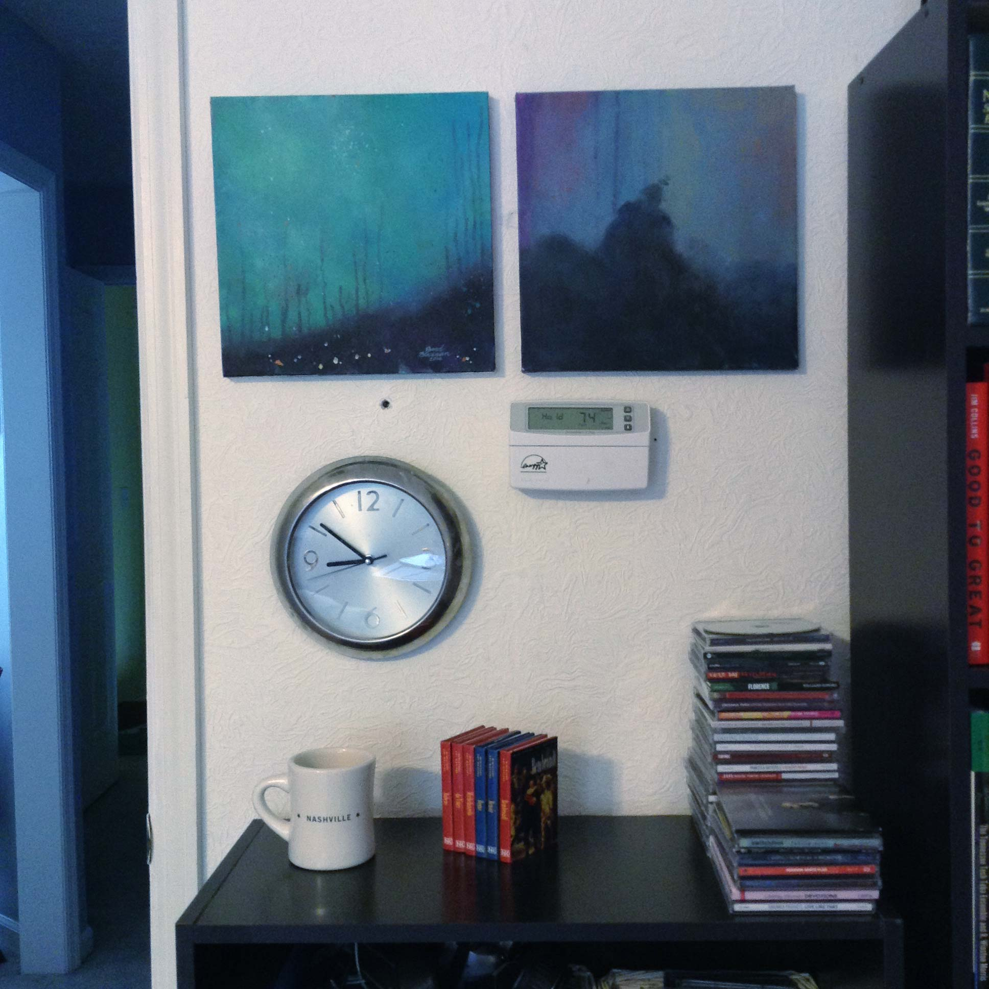 Two abstract paintings over a short bookcase