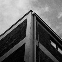 Image: black and white photo looking up at the corner of a building