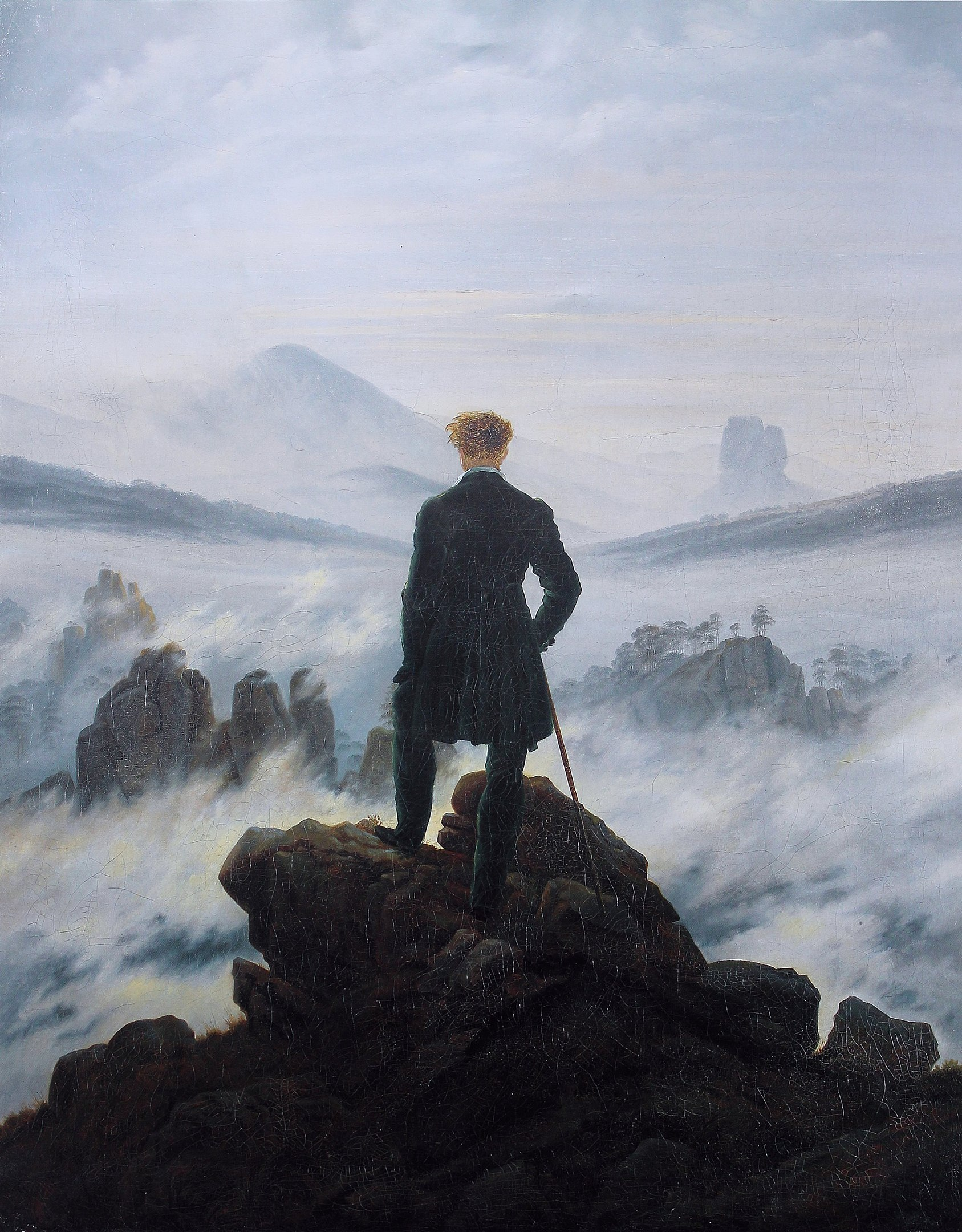 The hiker stands as a back figure in the center of the composition. He looks down on an almost impenetrable sea of fog in the midst of a rocky landscape - a metaphor for life as an ominous journey into the unknown.  By Caspar David Friedrich - The photographic reproduction was done by Cybershot800i. (Diff), Public Domain, https://commons.wikimedia.org/w/index.php?curid=1020146